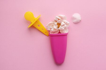 Rosebud and delicate petals in ice cream sculpt on a pink background. Space for text. flower composition