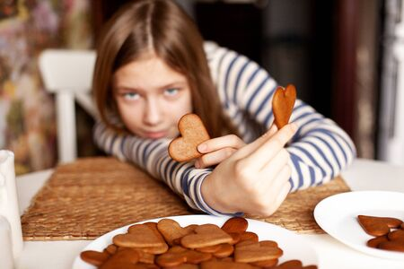 Smiling girl on blurry background holds heart-shaped cookies on outstretched arm, closeup Reklamní fotografie