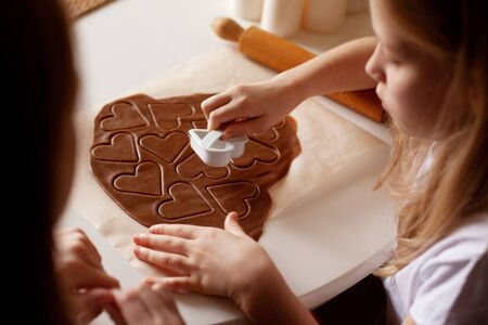 Children in the kitchen make homemade cookies cut out of heart-shaped dough. Close-up, top view