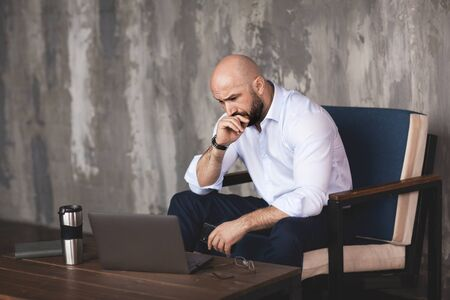 Confident man corresponds with colleagues in the messenger on the phone. Stylish businessman conducts business online using a laptop. Business portrait