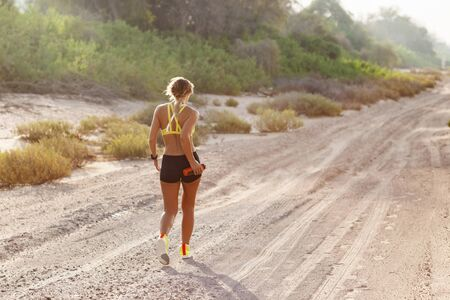 A young slender woman in sportswear runs on the sand against the background of trees on a Sunny day. Fitness, training, lifestyle, rear view