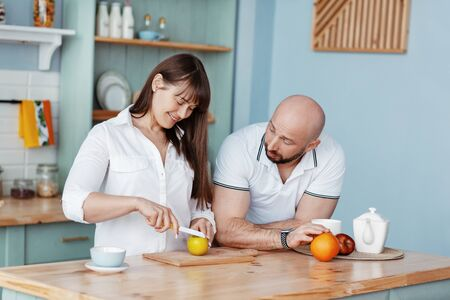 A young beautiful couple prepares Breakfast together in the kitchen on a weekend morning. Romantic relationships, love, family