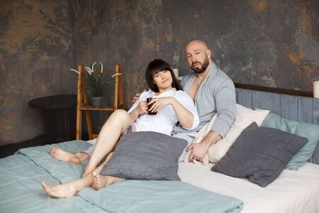 Cute young couple drinking morning coffee lying in bed. Love and relationships, husband and wife, boyfriend and girlfriend
