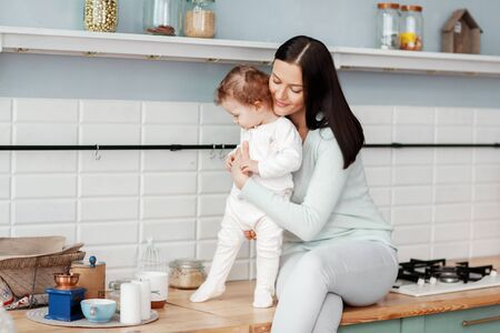 Beautiful young mother communicates and feeds the child in the kitchen at the table