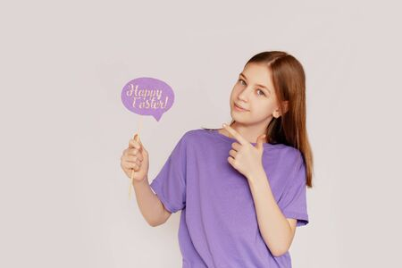 Portrait of a girl with a happy Easter sign in her hands on a light background with space for text. Concept of the Easter holiday