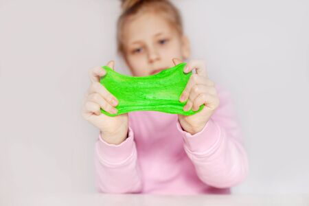 Cute girl playing with green slime. The girl holds in her hands and stretches the mucus . Slime toy, anti-stress toy 写真素材