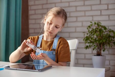 The girl uses an alcohol-based antiseptic hand gel while doing homework using a tablet. Prevention, hand disinfection, infection prevention, Covid-19 outbreak