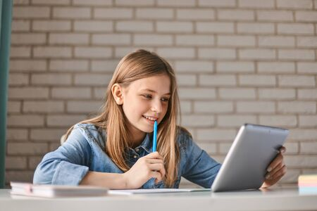 Cute teen schoolgirl does her homework with a tablet at home. The child uses gadgets for learning. Education, distance learning, home schooling during quarantine