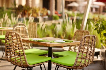 Terrace of a cozy cafe in green tones with wicker furniture under the open sky. Street cafe, street photo