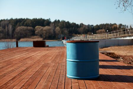 The blue barrel stands on the lake shore on a wooden pier. Spring landscape, blurred background