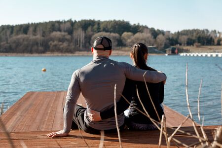 Back view of a young couple sitting on a pier on the lake and enjoying a beautiful spring landscape Stok Fotoğraf