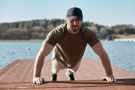 An adult athletic man performs push-UPS on a pier on the lake. A man is engaged in outdoor sports. Sports, fitness, lifestyle Фото со стока - 147144149