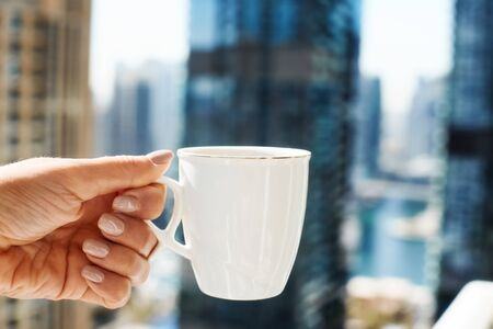 A girl holds a Cup of coffee against the background of modern buildings. A woman drinks morning coffee on the balcony during self-isolation