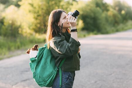 A charming young girl walks in nature, holding a backpack on her shoulder, from which her dog looks out, and holding a camera in her hands. A girl and her pet in search of beautiful frames