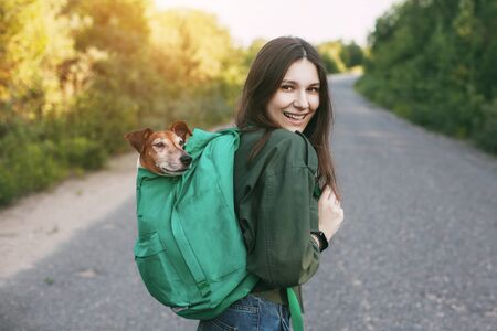A smiling girl is holding a green backpack on her shoulder, from which a cute dog looks out. A girl and her friend travel together, take walks. The concept of friendship and care 版權商用圖片