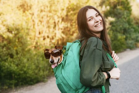 A smiling girl is holding a green backpack on her shoulder, from which a dog in sunglasses looks out. A girl and her friend travel together, take walks. The concept of friendship and care 版權商用圖片