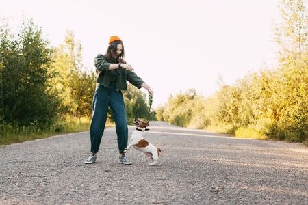 A beautiful teenage girl in a green jacket and orange hat plays with her dog while walking in the fresh air. The dog jumps up to get the flower that the girl is holding in her hands. Friendship, care, participation