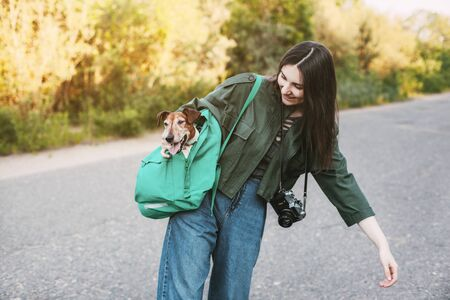 A smiling girl with a camera around her neck holds a green backpack on her shoulder, from which a cute dog looks out. A girl and her pet take photos of interesting places 版權商用圖片 - 150462628