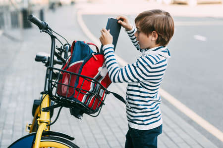 A cute boy in a striped sweater puts a tablet in a backpack that hangs on the handlebars of a Bicycle. The boy is going to ride home after school on a Bicycle.