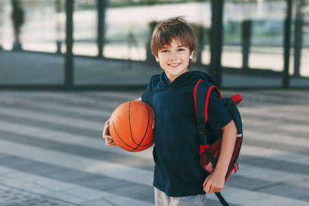 Portrait of a beautiful boy in sports uniform with a backpack and a basketball. The boy smiles and holds the ball in his hands. Training, education