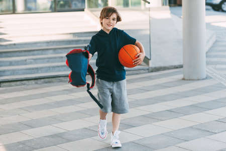 A cute boy with a backpack in one hand and a basketball in the other. The boy in shape in a hurry for a workout but basketball. Training, education