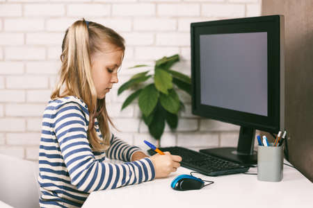 The schoolgirl sits at the computer and does her homework. The child learns from home.