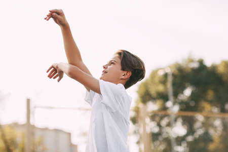 A teenage athlete throws a ball into the basket.