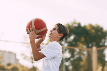 Close-up of a young athletes hands holding a basketball. The athlete is preparing to throw. Sport, athlete, healthy lifestyle