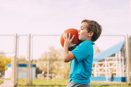 A cute boy in a sports uniform holds a basketball in his hands and prepares to throw