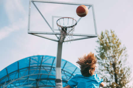 A boy in a sports uniform throws a ball into a basketball basket. A child plays basketball. Sports, lifestyle. Rear view, space for text