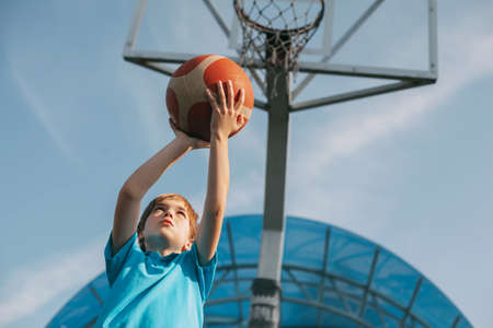 A boy in a sports uniform throws a ball into a basketball basket. A child plays basketball. Sports, lifestyle, place for text