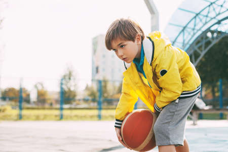 A cute boy in a yellow sports jacket throws a basketball. A child plays basketball. Sports, training, lifestyle