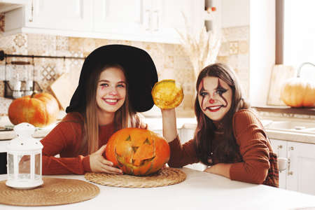 Two girls at home in the kitchen in costumes and makeup for Halloween sit with a pumpkin, play around and laugh. Happy kids are getting ready for Halloween. 免版税图像