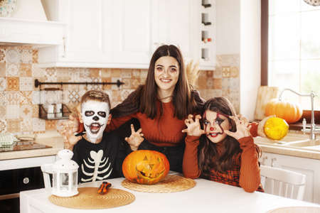 Happy kids celebrate halloween in kitchen at home in costumes and make-up with pumpkin lantern Jack looking at camera and smiling Foto de archivo