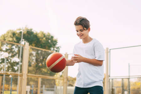 Funny cute boy athlete leads the ball in a game of basketball. A boy plays basketball after school. Sports, healthy lifestyle