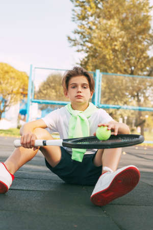 Cute teen sitting on the tennis court and resting after a workout. Sport, sportsman, lifestyle, leisure