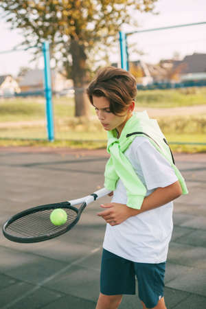 A young athlete is holding a tennis racket with a ball on it. Tennis player warms up before training. Sports, training, healthy lifestyle