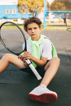 Portrait of a beautiful teenage boy with a tennis racket in his hands. A tennis player sits on the court and rests after training. Sport, sportsman, lifestyle, leisure