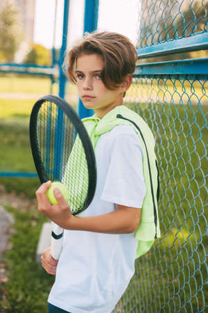 Portrait of a beautiful teenage boy standing with a tennis racket and a ball in his hands. Tennis player resting after training. Sport, sportsman, lifestyle, leisure