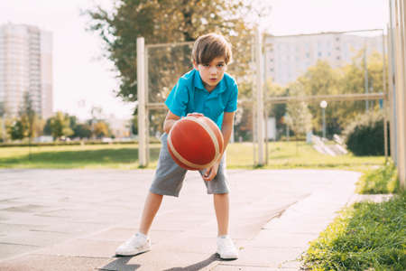 Focused cute boy athlete leads the ball in a game of basketball. A boy plays basketball after school. Sports, healthy lifestyle, leisure Stock Photo