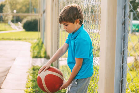 A cute boy in a blue t-shirt is holding an orange basketball. The athlete is resting during the game. The concept of a healthy lifestyle