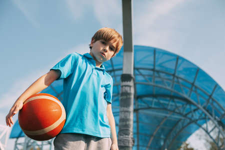 Portrait of a boy in a sports uniform with a basketball in his hands. A boy holds a ball in his hands after playing basketball. Sports, education, healthy lifestyle Stock Photo
