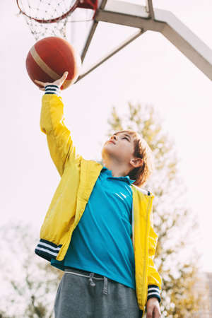 Portrait of a cute boy basketball player standing with a ball in his hands next to the basketball Hoop. The concept of sport and a healthy lifestyle Stock Photo