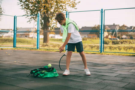 A young athlete takes a ball from a sports bag, holds a tennis racket in his hand and prepares to hit