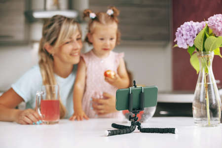 Close-up of a phone on a tripod on the kitchen table in the background, happy mom and daughter are sitting at the table in the kitchen and watching educational videos
