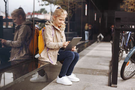 After school, a smiling and cute girl sits on a step near a glass building while waiting for the bus, studies on a tablet online and communicates via video.