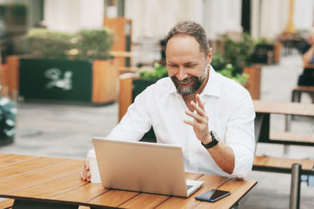 An adult man sits on the street in a cafe, communicates on the network and works on a laptop.