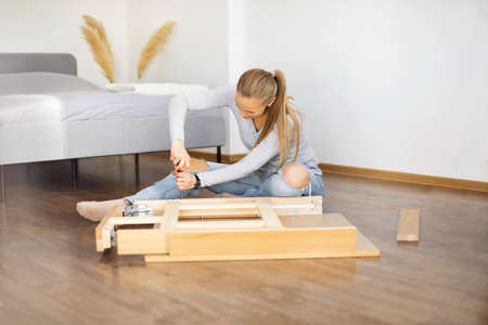 Young woman collects new furniture at home after renovation