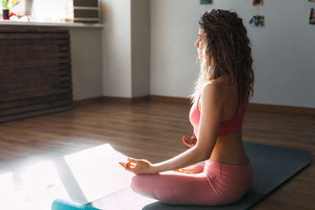 A young girl with her eyes closed meditates in the lotus position in the classroom.Sports, fitness, yoga. Side view, space for text