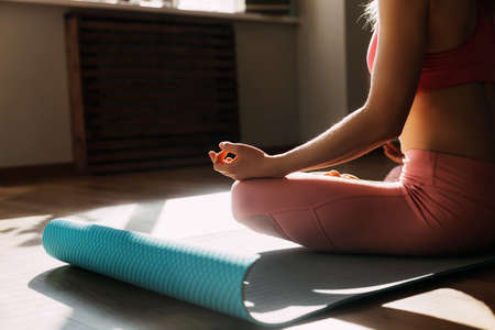 A young woman sits in the lotus position and meditates at home or in a yoga class and meditates. Healthy lifestyle, yoga, meditation